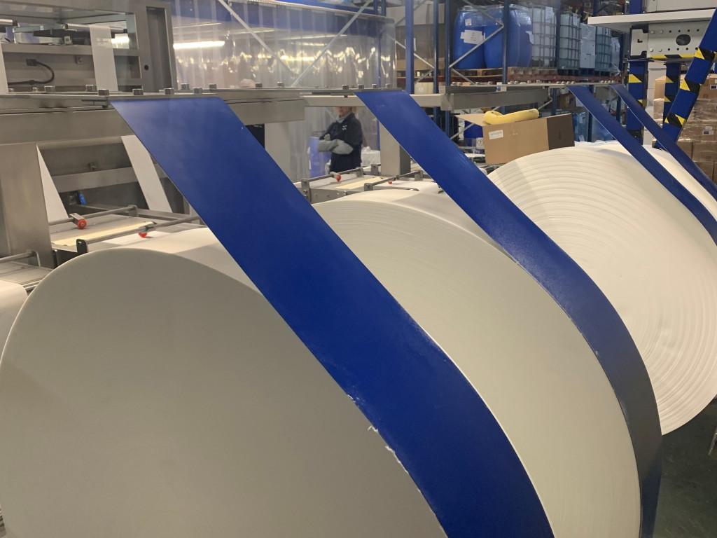 A close-up of a folding machine at work