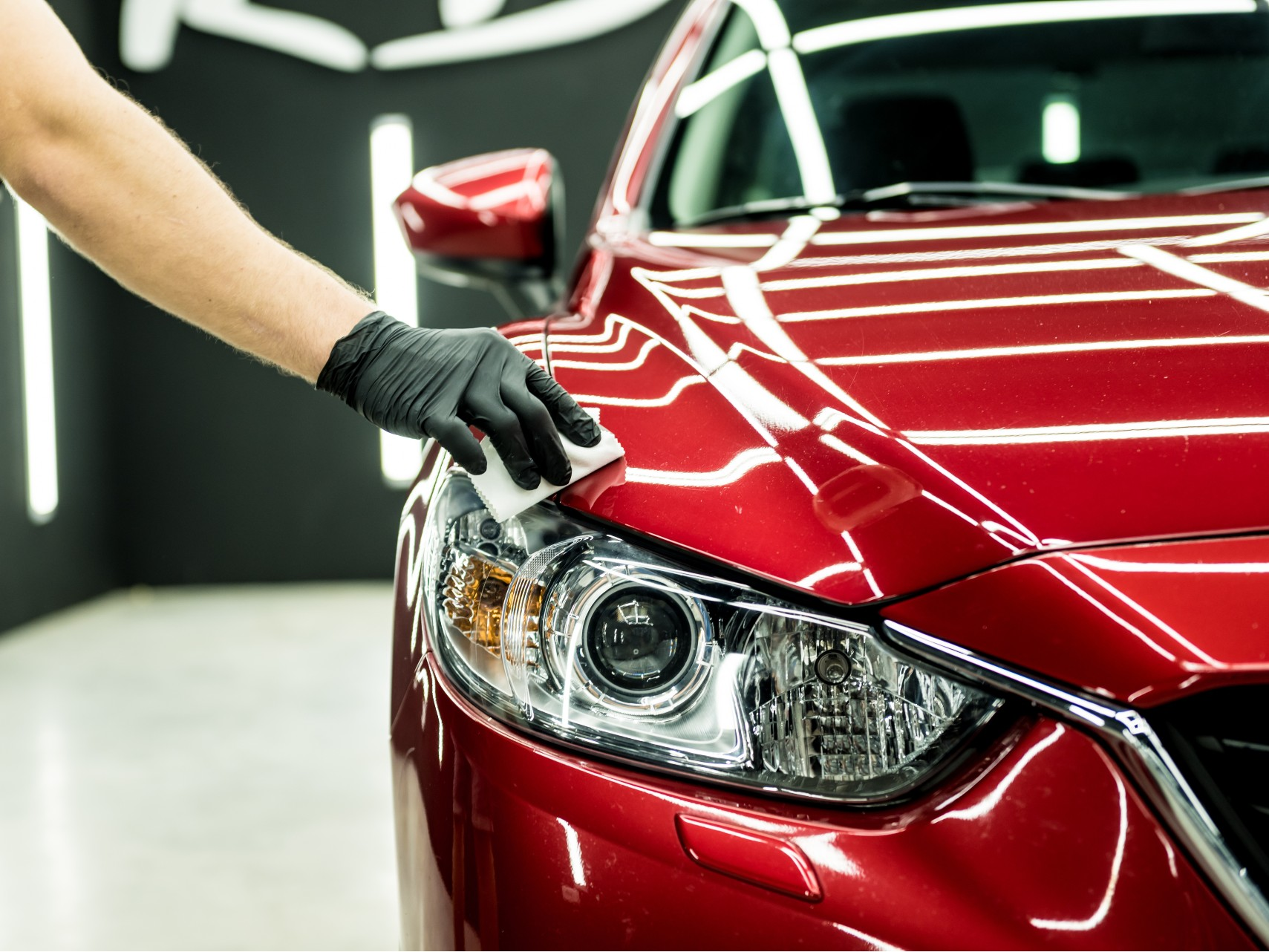 A picture of automotive wet wipes being used on a car